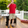 Man drinking beer on outdoor patio — Stock Photo