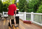 Mature man turning on barbecu grill while outside on open deck  — Stock Photo