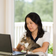 Mature woman relaxing with her cat while working at home — Stock Photo #48421623