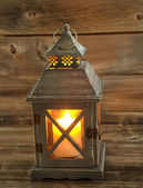 Asian Lantern and glowing white candle inside on weathered wood — Stock Photo