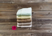 Clean Towels and single pink flower on Weathered Wood — Stock Photo