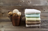 Clean stacked Towels and Bucket filled with Decorations on Weath — Stock Photo