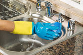 Cleaning inside of kitchen sink with soapy water and sponge  — Stock Photo