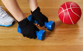 Woman working out with small weights on wooden gym floor  — Stock Photo
