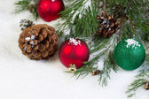Christmas Ornaments on Snow with Pine Tree Branch  — Stockfoto