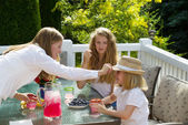 Mother putting hat on younger daughter during breakfast outdoors — Stock Photo