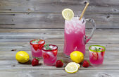 Large pitcher of lemonade with glassware — Stock Photo