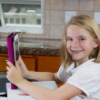 Pretty young girl doing her homework in the kitchen — Stock Photo #50680889