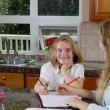 Sisters doing their homework while in the kitchen — Stock Photo #50680911