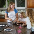 Mother and daughters making cookies from raw dough — Stock Photo #50895993