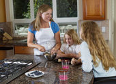Mother and daughters making cookies from raw dough — Foto Stock