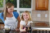 母と娘のクッキーをオーブンに入れて — ストック写真