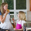 Mom and daughter enjoying freshly baked cookies in the Kitchen — Stock Photo #51008259