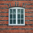 White painted wood arced window in a red brick wall — Stock Photo