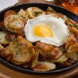 Fried potatoes with an egg in a frying pan — Stock Photo