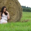 Girl next to haystack - Stock Photo