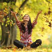 Donna caduta foglie in autunno parco — Foto Stock