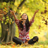 Woman drop leaves in autumn park — Stockfoto