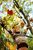 woman drop leaves in autumn park — Stock Photo