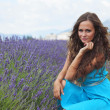 Woman sitting on a lavender field - Stock Photo