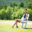 Young woman sitting on the bench in park — ストック写真