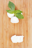 Sliced mozzarella on wooden board — Stock Photo