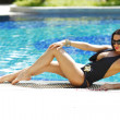 Womsitting on ledge of pool — Stock Photo #14129061