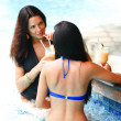 Two women with cocktails in swimming pool - ストック写真