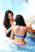 Two women with cocktails in swimming pool — Stock Photo