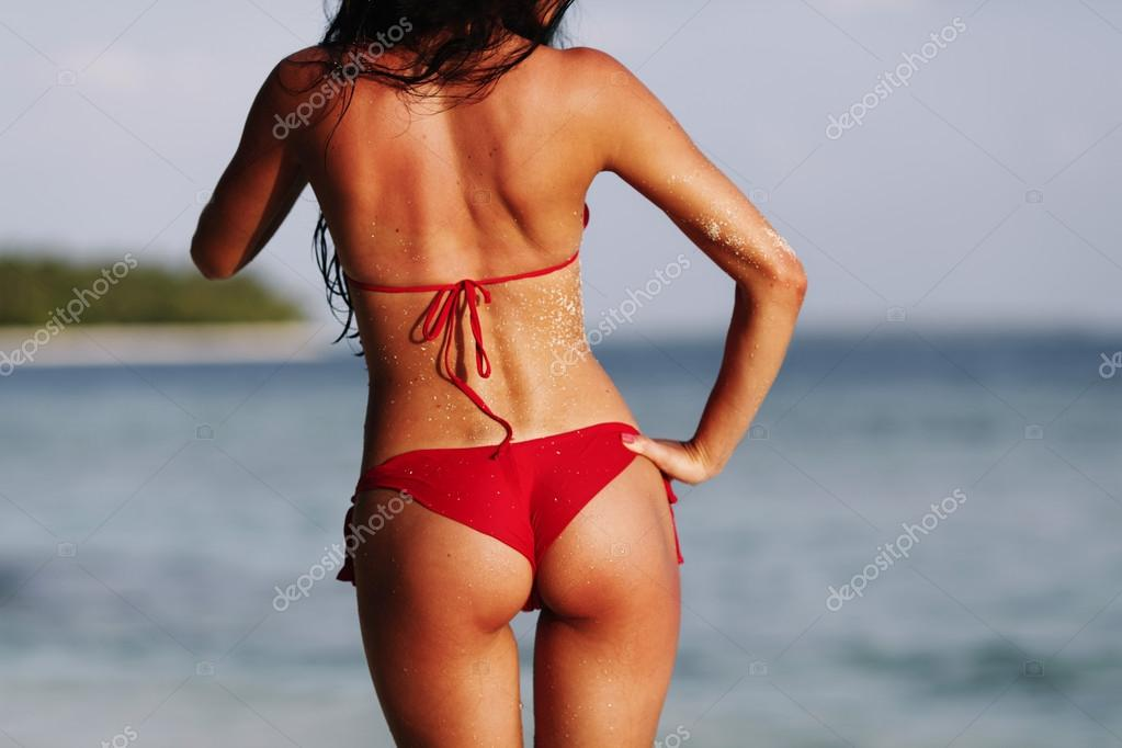 Sexy back of a beautiful woman in red bikini on sea background — Stock Photo #14128910