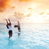 Happy women playing in water — Stockfoto