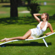 Girl sitting in a white lounge on a green grass — Stock Photo