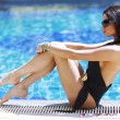 Woman sitting on the ledge of the pool - Foto Stock