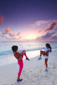Two women stretching on beach — Stock Photo