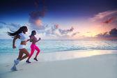 Two women running on beach — Stock Photo