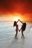 Two women enjoying sunset on beach — Stock Photo