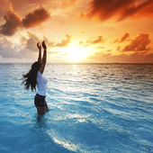 Woman in sea on sunset — Stock Photo