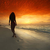 Femme qui marche sur la plage — Photo