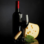Red wine and cheese on black — Stock Photo