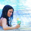 Woman in swimming pool with cocktail — Stock Photo
