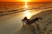 Woman in chaise-lounge relaxing on beach — Stock Photo
