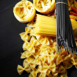 Pasta ingredients on black table - Stock Photo