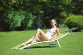 Yeşil çimenlerin üzerinde beyaz bir salonda oturan kız — Stok fotoğraf