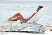 Woman in chaise-lounge near sea — Stock Photo