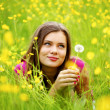 Woman blow on dandelion — Stock Photo