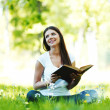 Woman reading book outdoors — Stock Photo