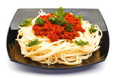 Spaghetti bolognese on black plate — Stock Photo
