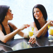 Two women with cocktails in swimming pool — Stock Photo #33272723