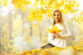 Woman sitting on autumn leaves — Stock Photo