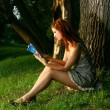 Young beautiful Woman sitting under the tree in forest — Stock Photo #34741991